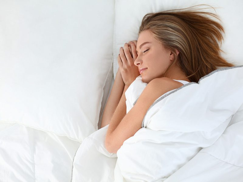 Overhead view of a young woman sleeping in bed with large white pillows and comforter