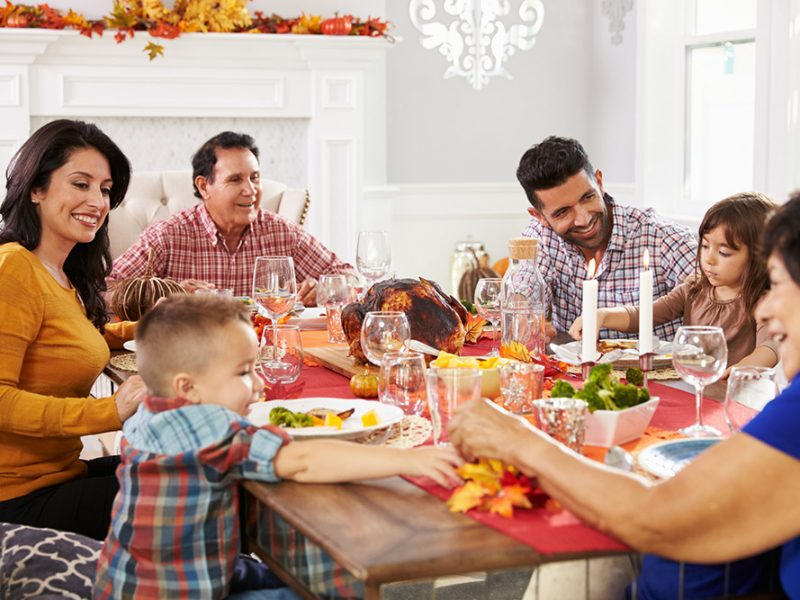 A family sitting around the table at Thanksgiving with two young children and everyone laughing
