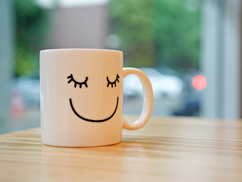Close up of a white coffee mug on a table with a smiling sleeping face on it with eyelashes