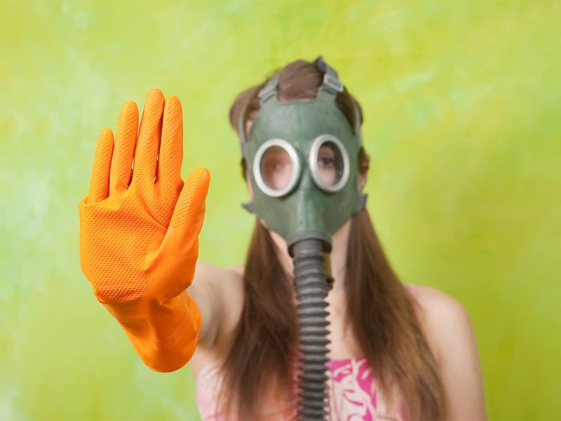 Young woman wearing a gas mask and orange rubber gloves with her hand up and distancing herself