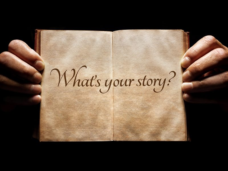 Hands holding an open antique book in the dark with what's your story written on the pages