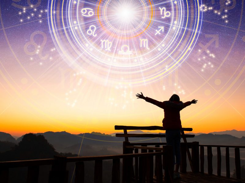 Silhouette of a person at sunset with their arms outstretched and looking at the sky with a horoscope chart around the sun