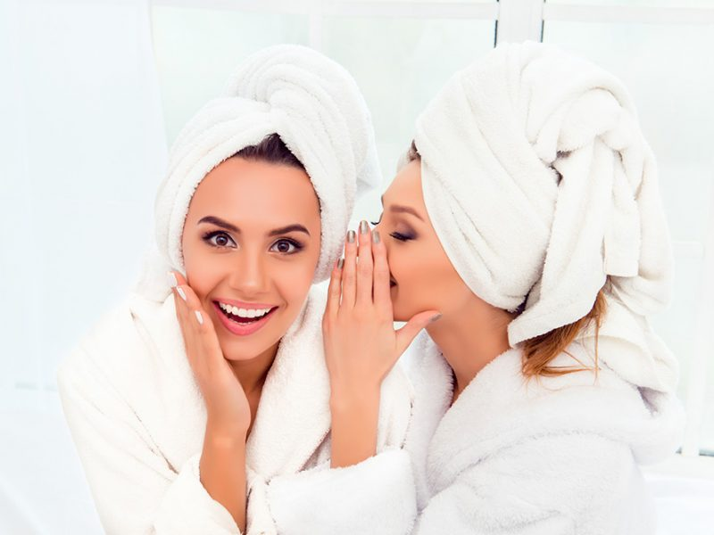 Two young women in a white room wearing fluffy white robes and their hair wrapped in towels one of them whispering in the other's ear and they are both smiling