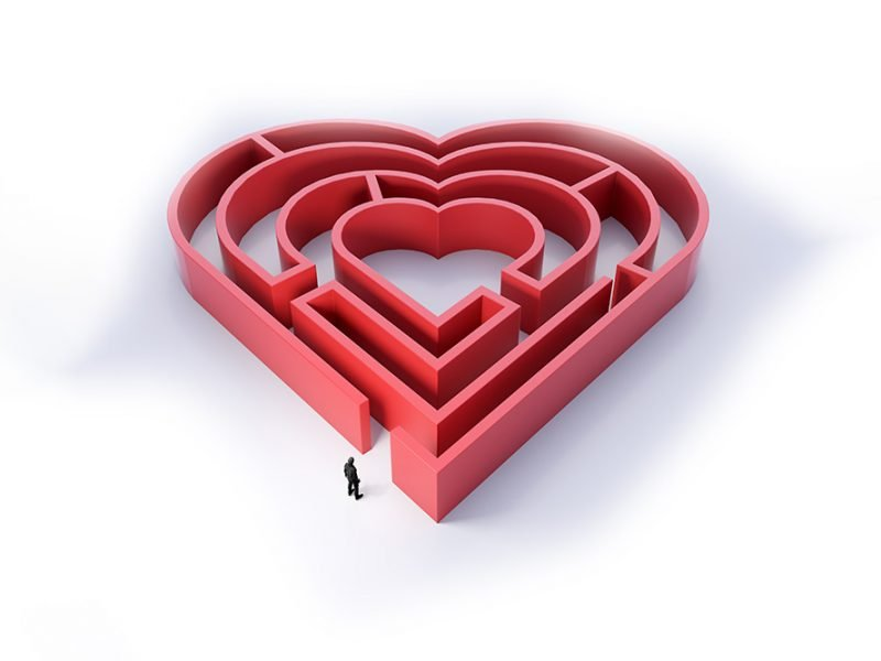 Vector image of a large maze in the shape of a heart with the small silhouette of a person at the bottom entering the maze