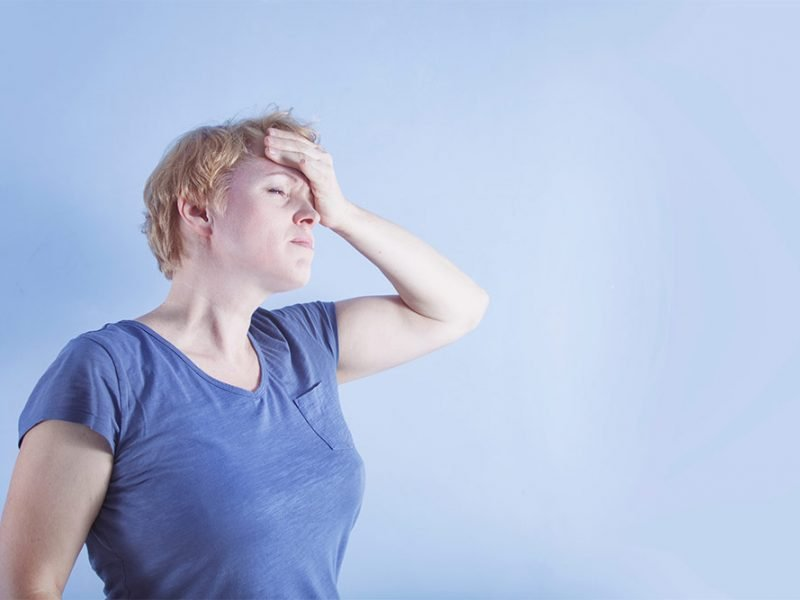 A woman standing in front of a pale blue background with her eyes closed and hand to her forehead like she's stressed